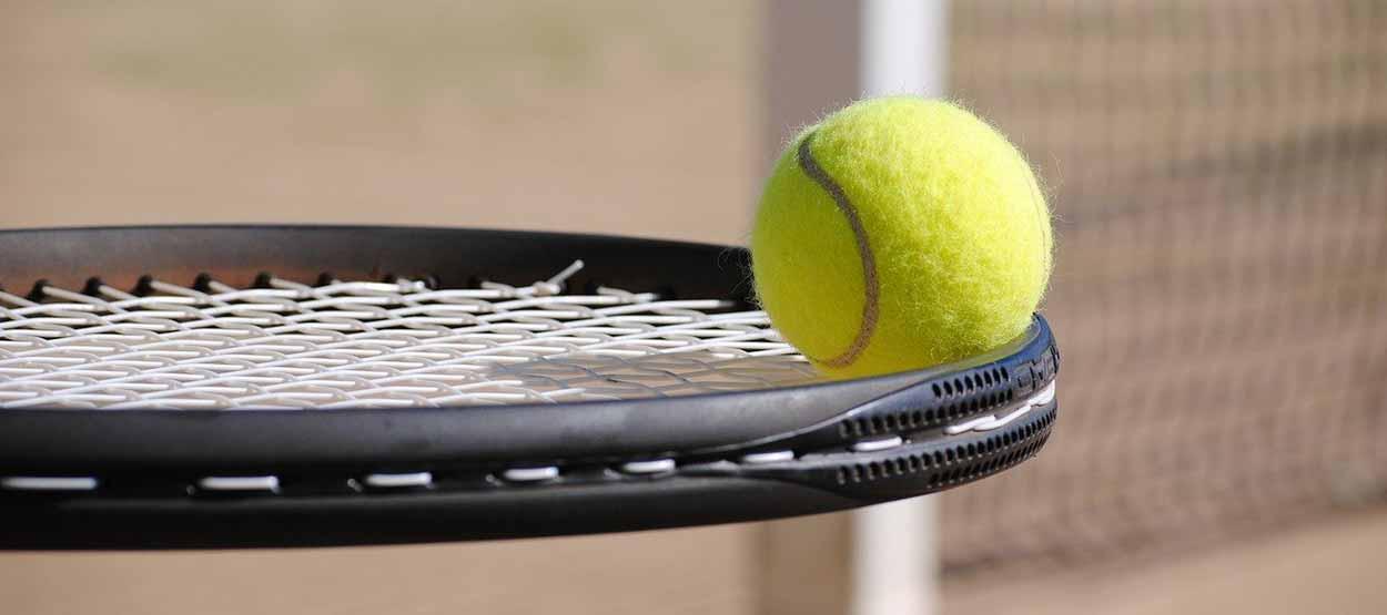 Tennisschläger balanciert Tennisball
