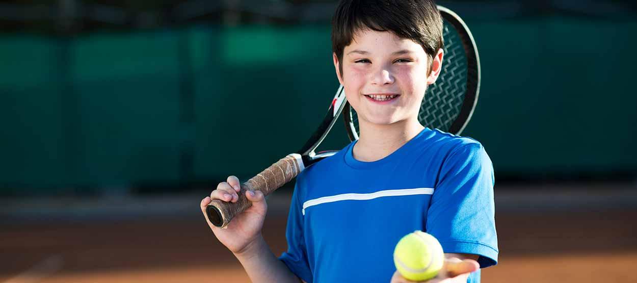 Kind mit Tennisschläger und Ball lächelt den Betrachter an