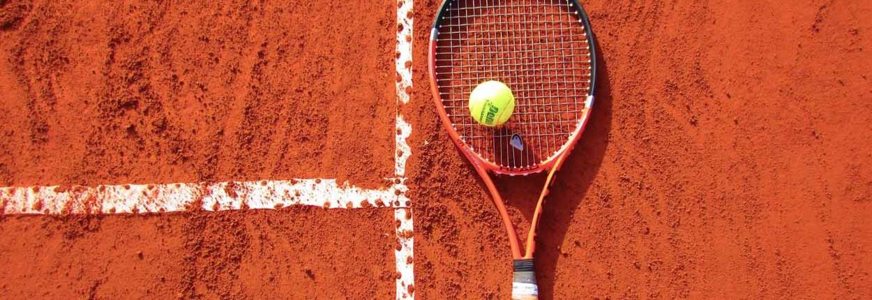 Tennisschläger und Tennisball liegen auf einem Spielfeld